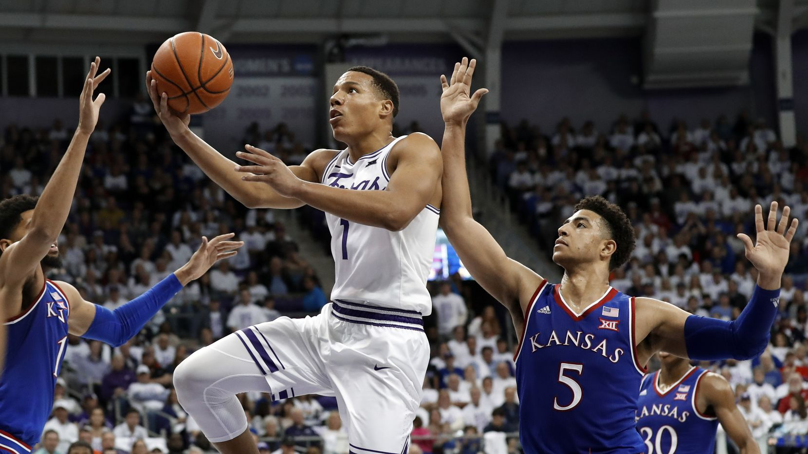 Kansas forward Dedric Lawson (1) and guard Quentin Grimes (5) defend as TCU guard Desmond Bane (1) leaps to the basket for a shot in the second half of an NCAA college basketball game in Fort Worth, Texas, Monday, Feb. 11, 2019.