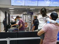 Un grupo de pasajeros pasa por un punto de revisión de TSA en el aeropuerto Dallas - Fort Worth.
