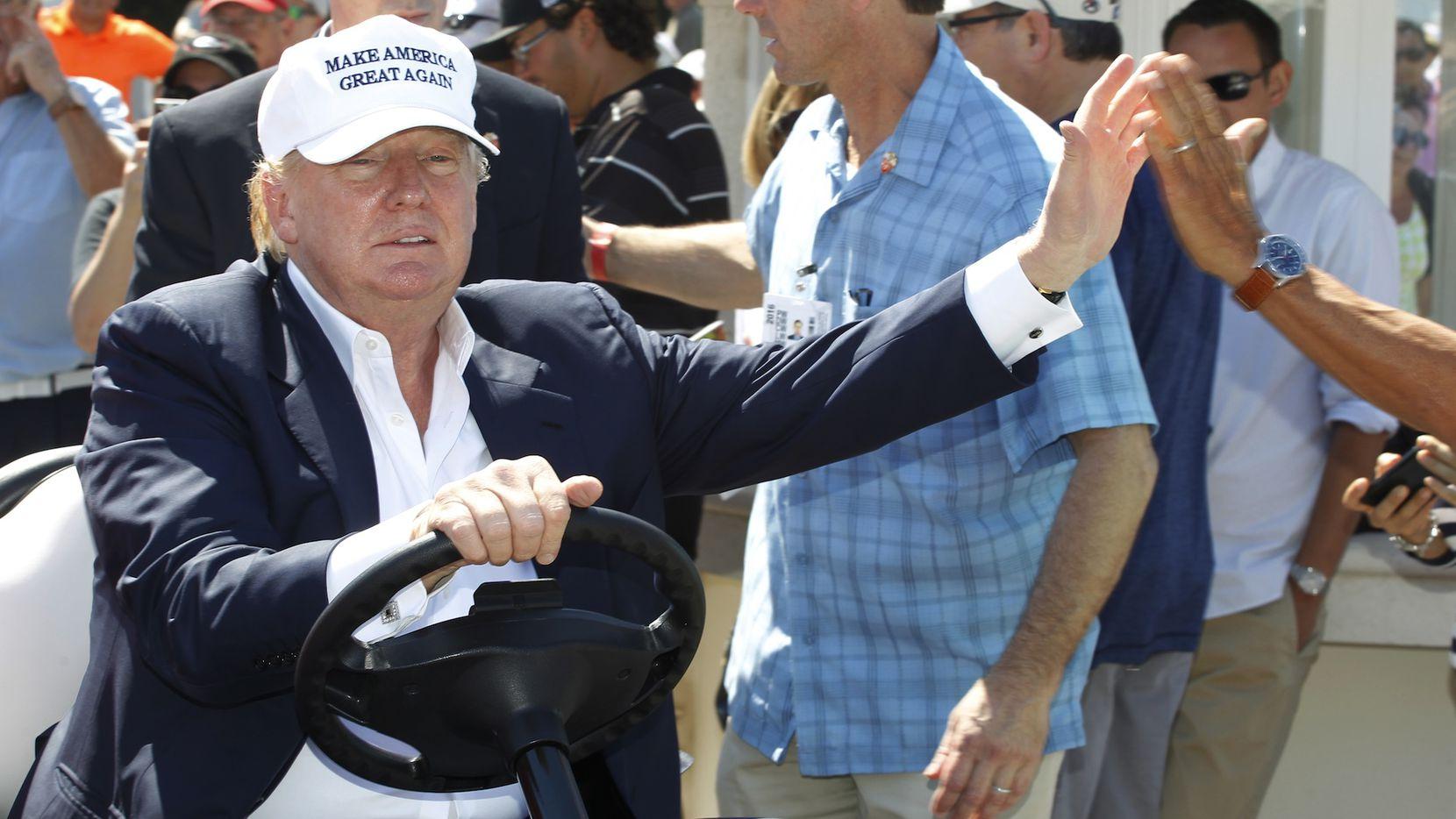 Donald Trump maneja un carro de golf en su campo de golf Mar-a-Lago en Doral, Florida.