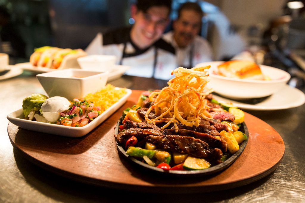 A steak fajita skillet topped with fried onion strings is one of the dishes offered by father-and-son chefs Julian and Beto Rodarte at their Beto and Son restaurant in Trinity Groves.