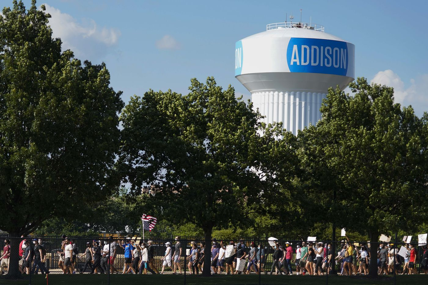 Demonstrators march through Addison Circle Park during a protest on Thursday, June 4, 2020, in Addison. Protests continued Thursday in the response to the death of George Floyd.