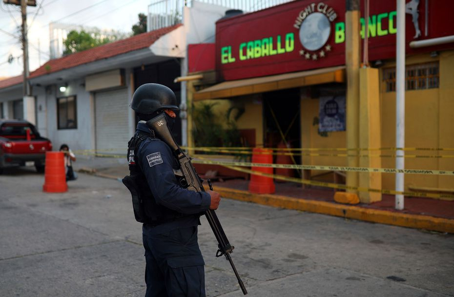 A police officer guards the scene outside a bar where more than 20 people died in an overnight attack, in Coatzacoalcos, Mexico, early Wednesday, Aug. 28, 2019.