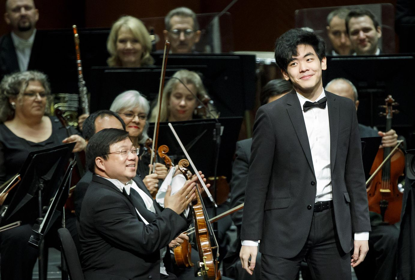 Members of the the Fort Worth Symphony Orchestra applaud Daniel Hsu of the USA as he takes the stage for the final performance of the Van Cliburn International Piano Competition at Bass Performance Hall on Saturday, June 10, 2017, in Fort Worth. (Smiley N. Pool/The Dallas Morning News)