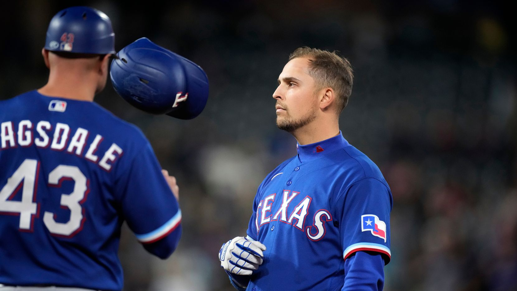 Texas Rangers' Nate Lowe, right, tosses his batting helmet to first base coach Corey Ragsdale after Lowe flied out in the eighth inning of the team's baseball game against the Colorado Rockies on Tuesday, June 1, 2021, in Denver.