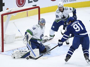 Vancouver Canucks goaltender Braden Holtby (49) stops Toronto Maple Leafs centre John Tavares (91) during third period NHL hockey action in Toronto on Monday, February 8, 2021. THE CANADIAN PRESS/Nathan Denette/The Canadian Press via AP)