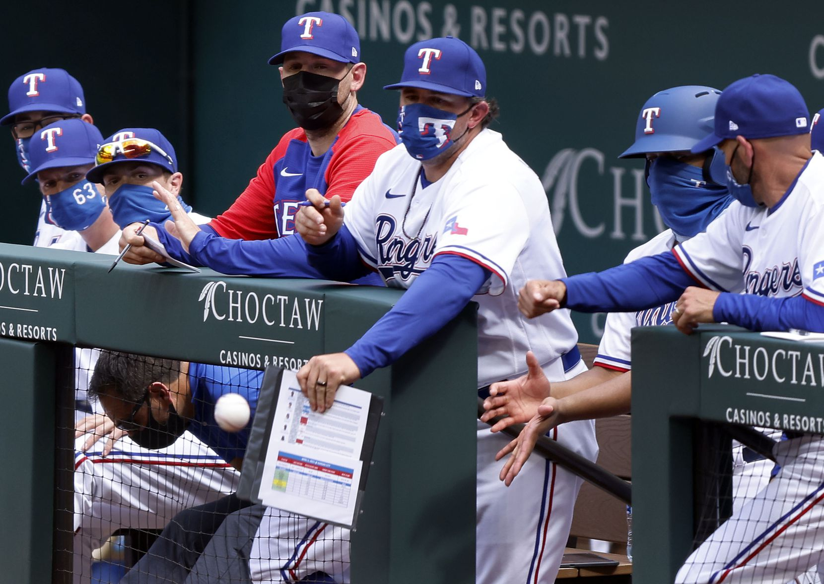 A Texas Rangers coach deflects a foul ball off his clip board during their Opening Day game at Globe Life Field in Arlington, Monday, April 5, 2021. (Tom Fox/The Dallas Morning News)