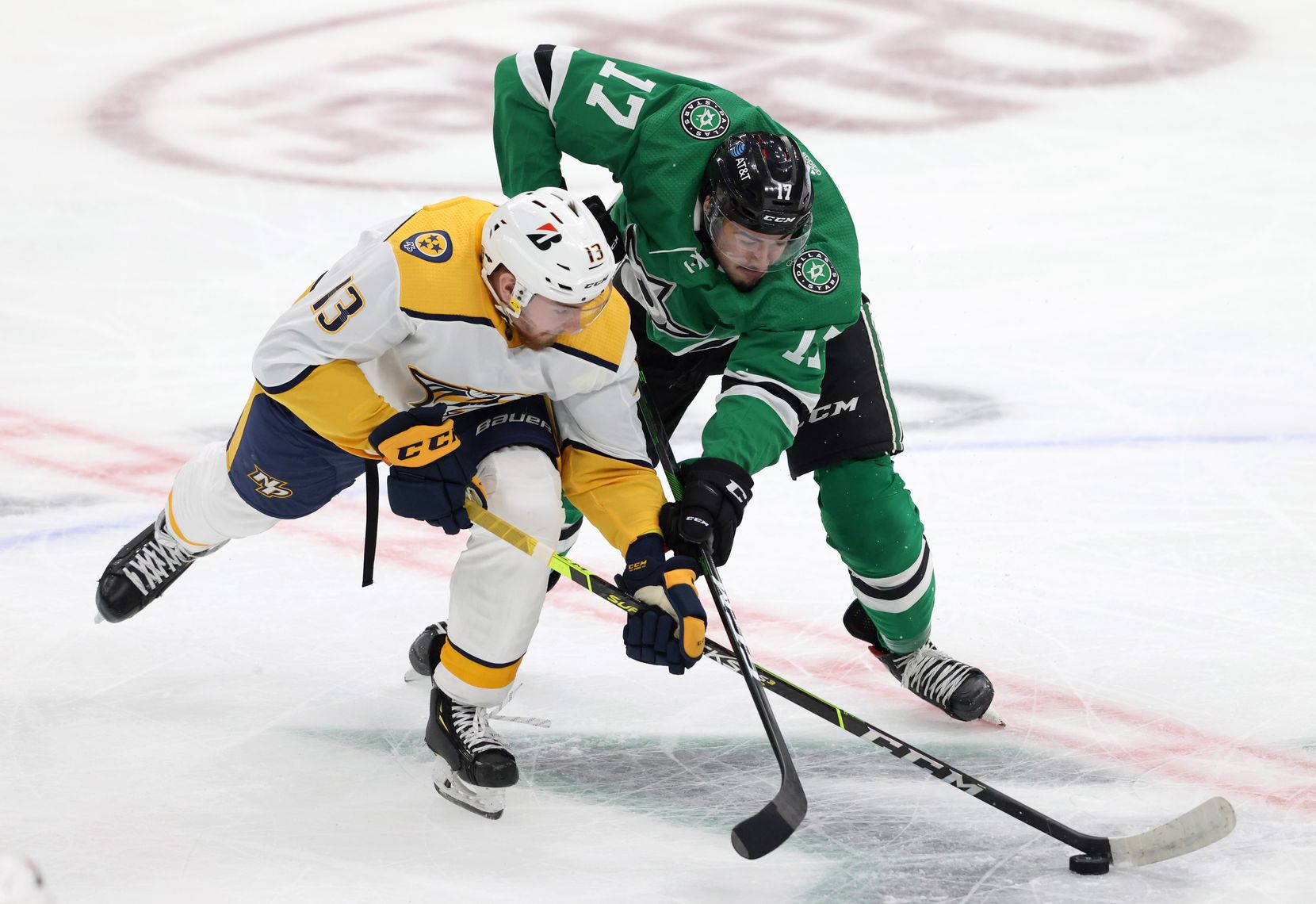 Dallas Stars Nicholas Caamano (17) and Nashville Predators center Yakov Trenin (13) fight for possession during the second period of play in the Stars home opener at American Airlines Center on Friday, January 22, 2021in Dallas. (Vernon Bryant/The Dallas Morning News)