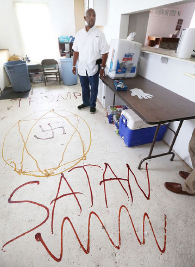 """Pastor Kenneth McNeil shows Nazi symbolism, along with the words """"Satan"""" and """"Trump"""" written with mustard and ketchup on the floors of the Willow Grove Baptist Church's fellowship hall. (Rod Aydelotte/Waco Tribune-Herald)"""