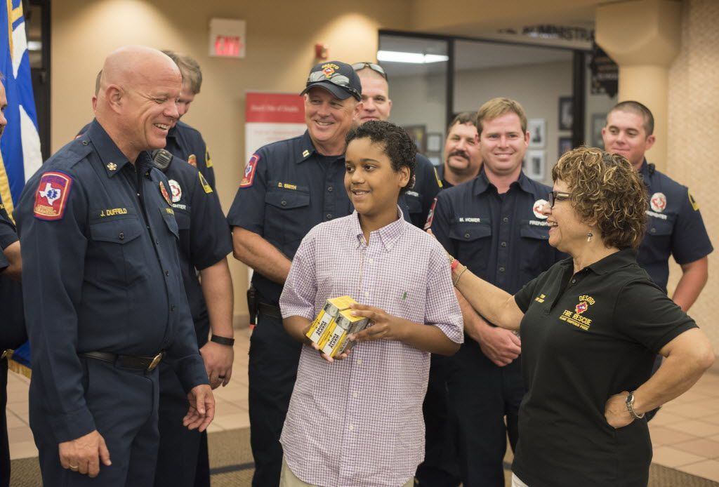 DeSoto Fire Rescue Chief Jerry Duffield, left, talks with Hector Montoya, 11, right,  for his donation of 125 smoke detectors to the department on Wednesday, Aug. 3, 2016.     (Rex C. Curry/Special Contributor)