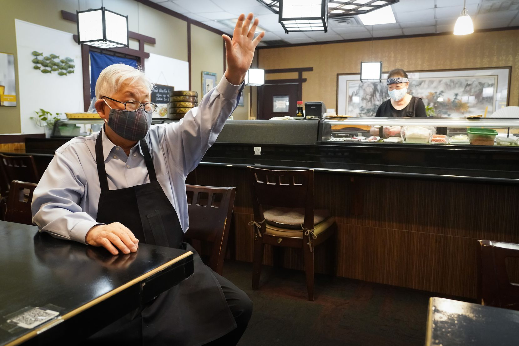 """Sushiya restaurant owner Kang Lee waved to a departing customer as Junok Kim worked the sushi bar April 15 in Dallas.  Lee's grandson had  posted a TikTok video asking people to come support his grandfather's struggling restaurant. It went viral and led to a surge in business. """"I couldn't believe it,"""" Lee said. """"People were lined up at the door!"""""""