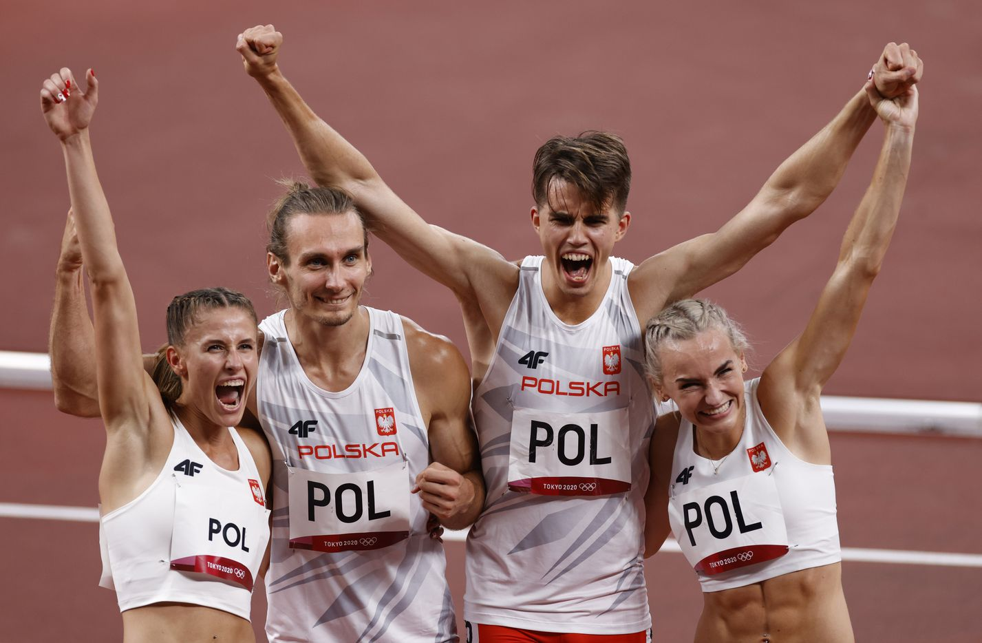 (From l to r) Poland's Natalia Kacmarek, Karol Zalewski, Kajetan Duszynski and Justyna Swiety-Ersetic pose for photographers after setting an Olympic record after winning the mixed 4x400m relay final during the postponed 2020 Tokyo Olympics at Olympic Stadium, on Saturday, July 31, 2021, in Tokyo, Japan. (Vernon Bryant/The Dallas Morning News)