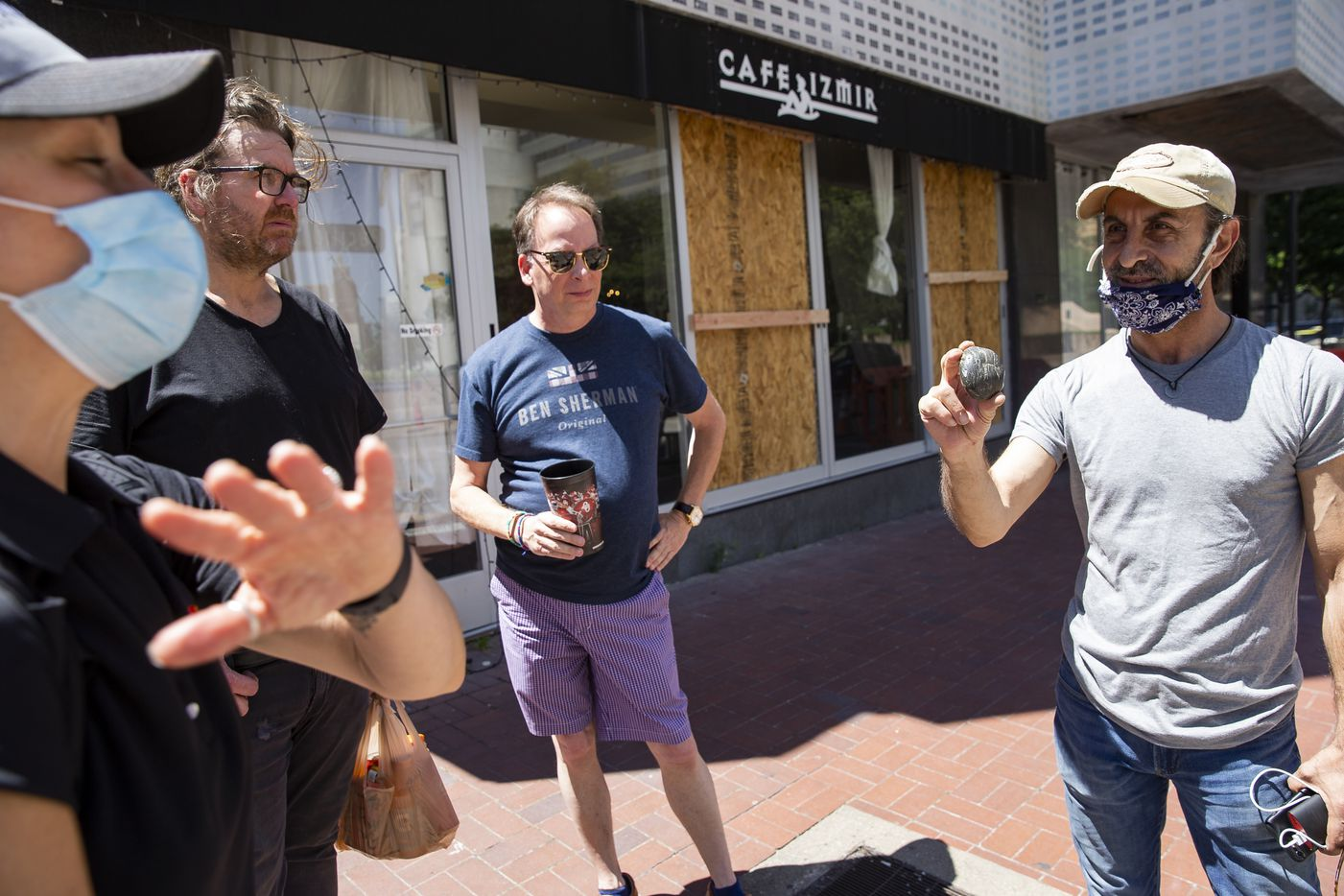 Cafe Izmir owner Beau Nazary shows Kourtney Garrett, President and CEO of Downtown Dallas Inc, a rock that was thrown through his cafe last night on Saturday morning, May 30, 2020, in Dallas. Nazary said he showed up to looters drinking beer last night at 11:30 and stayed until five in the morning watching over his business.