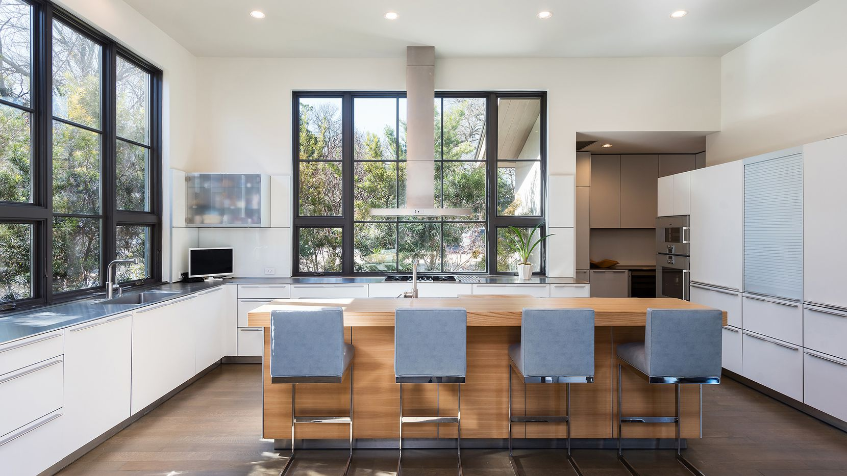 An open kitchen with clean lines such as this one in Bluffview is typical of transitional design in Dallas neighborhoods.