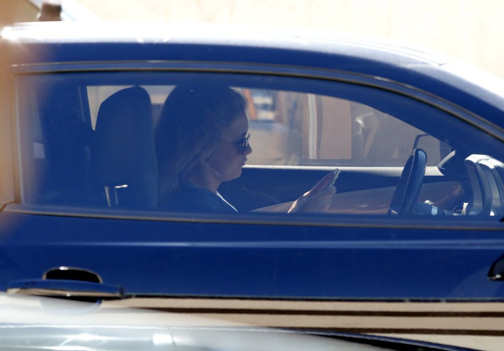 A women looks at her phone while driving down Central Expressway in Dallas on July 16, 2015. (Rose Baca/The Dallas Morning News)