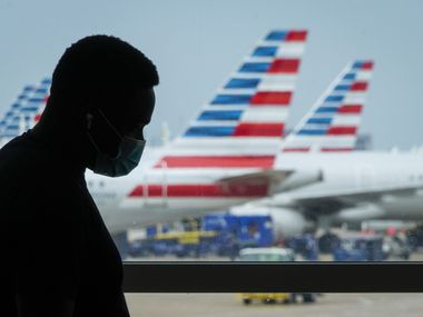A man wearing face covering waits at a gate at Terminal E as American Airlines planes are seen at Terminal C on Wednesday, Sept. 8, 2021, at DFW Airport. (Smiley N. Pool/The Dallas Morning News)
