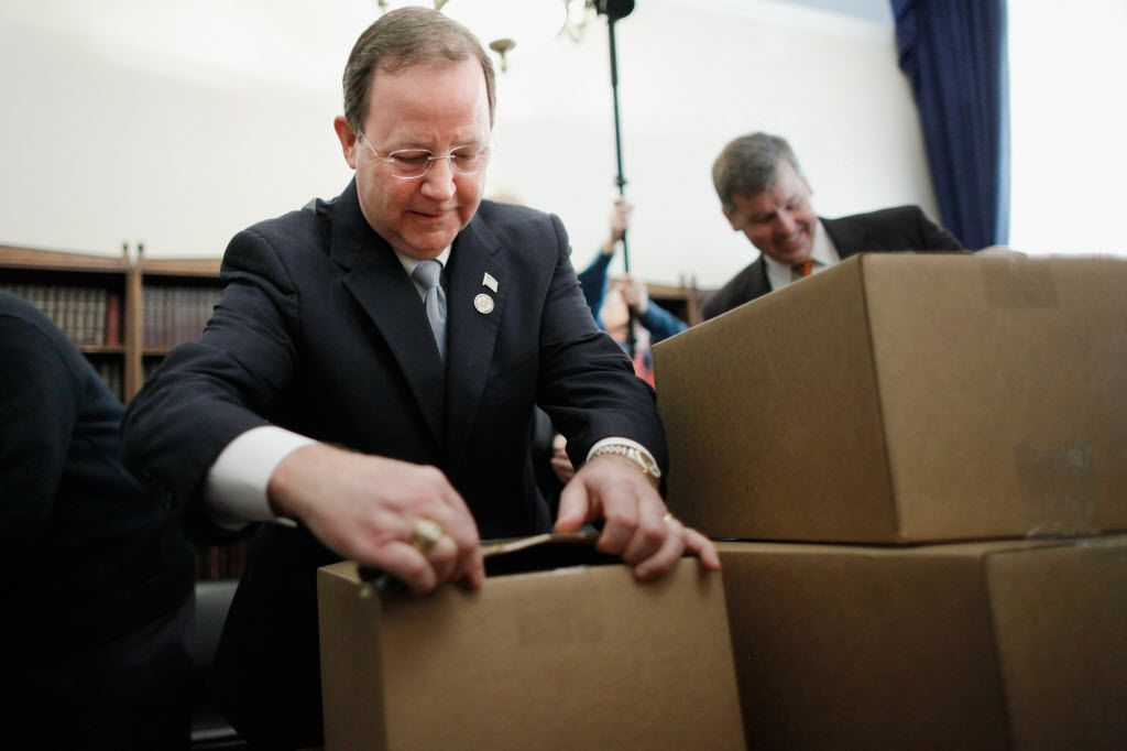 House Budget Committee member  Rep. Bill Flores used his keys to open boxes of President Barack Obama's proposed fiscal year 2012 federal budget in Washington on Feb. 14, 2011.
