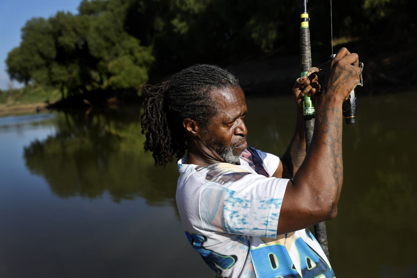 Odell Allen reels in his line to find he caught a softshell turtle instead of an alligator gar on the Trinity River near the Westmoreland bridge, Monday, August 30, 2021.  (Tom Fox/The Dallas Morning News)