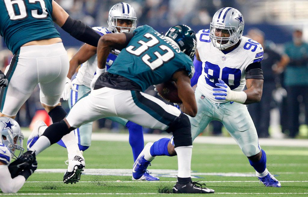 FILE - Cowboys defensive end Demarcus Lawrence (90) assist on a tackle of Philadelphia Eagles running back Josh Adams (33) in the first quarter at AT&T Stadium in Arlington, Texas, Sunday, December 9, 2018. (Tom Fox/The Dallas Morning News)