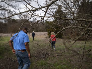 John Jenkins, Dallas Park and Recreation director, heads into the Woody Branch greenspace with, in the distance, Park Board President Calvert Collins Bratton and Robert Kent, Texas state director for The Trust for Public Land.