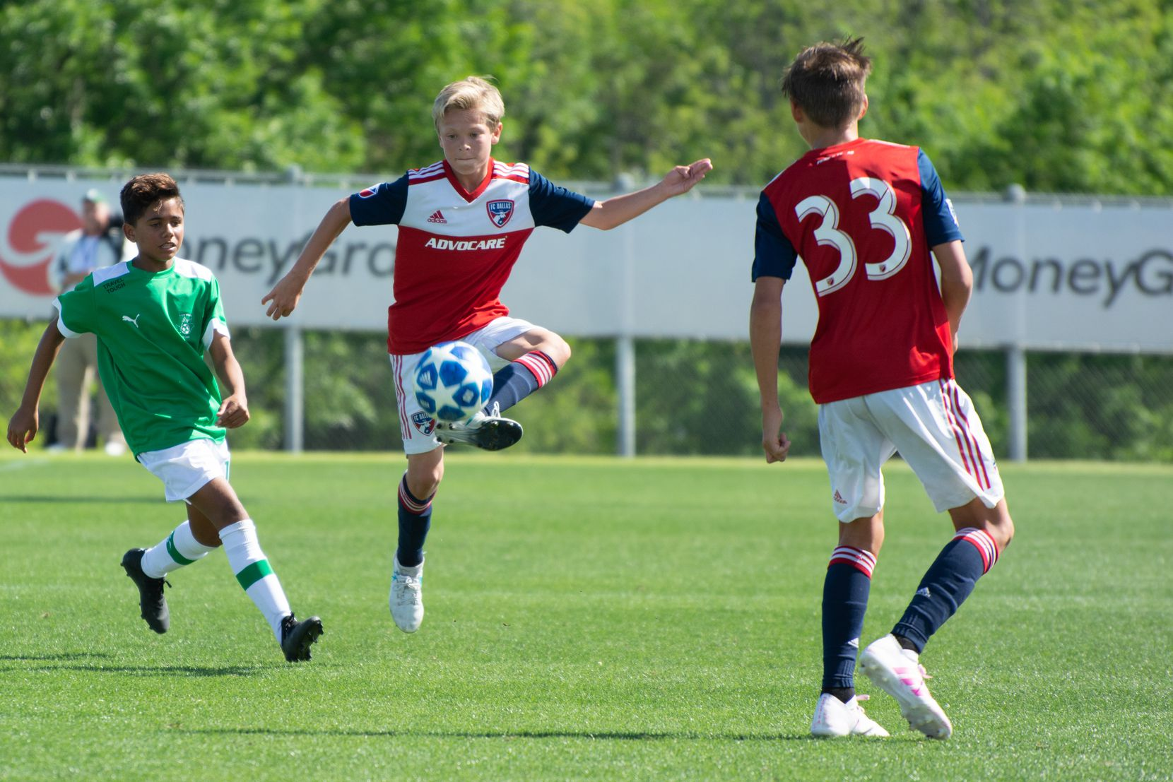 Nolan Norris traps the ball against Ikapa United in the 2019 Dallas Cup Super 14s while Nighte Pickering looks on.