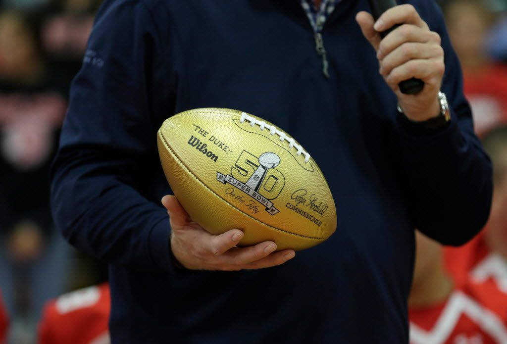 In this photo released by the NFL, former Cincinnati Bengals quarterback Boomer Esiason presents the NFL Super Bowl High School Honor Roll gold ball at East Islip High School, Friday, Oct. 9, 2015 in Islip Terrace, NY. (Adam Hunger/AP Images for National Football League)