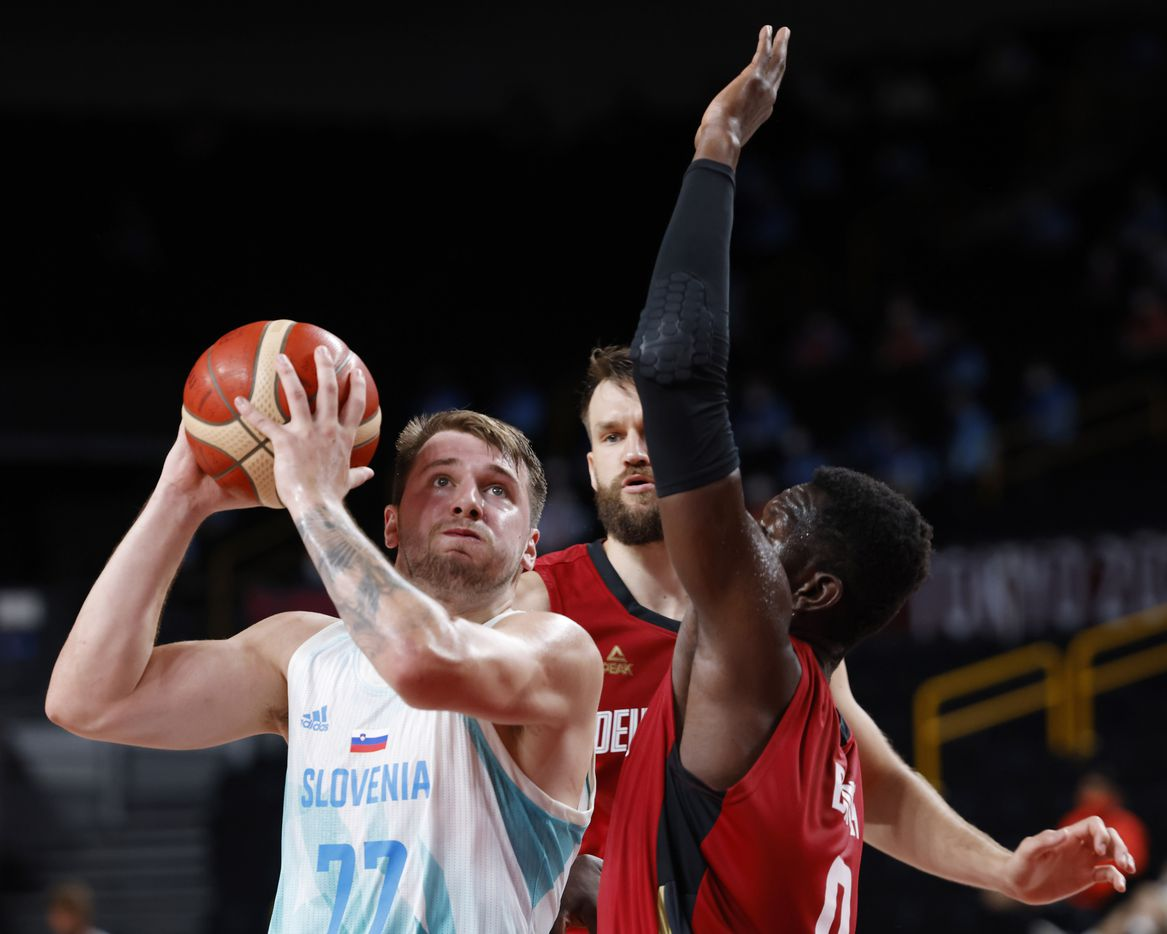 Slovenia's Luka Doncic (77) drives in between Germany's Danilo Barthel (22) and Isaac Bonga (0) during the second half of play of a quarter final basketball game at the postponed 2020 Tokyo Olympics at Saitama Super Arena, on Tuesday, August 3, 2021, in Saitama, Japan. (Vernon Bryant/The Dallas Morning News)