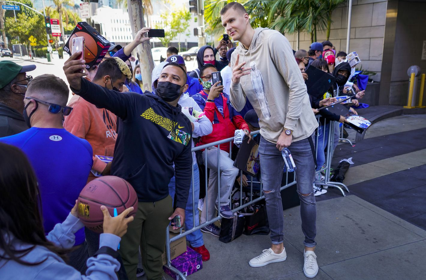 Dallas Mavericks center Kristaps Porzingis poses for a selfie with fans as the team leaves their hotel before Game 7 of an NBA playoff basketball series against the LA Clippers at the Staples Center on Sunday, June 6, 2021, in Los Angeles.