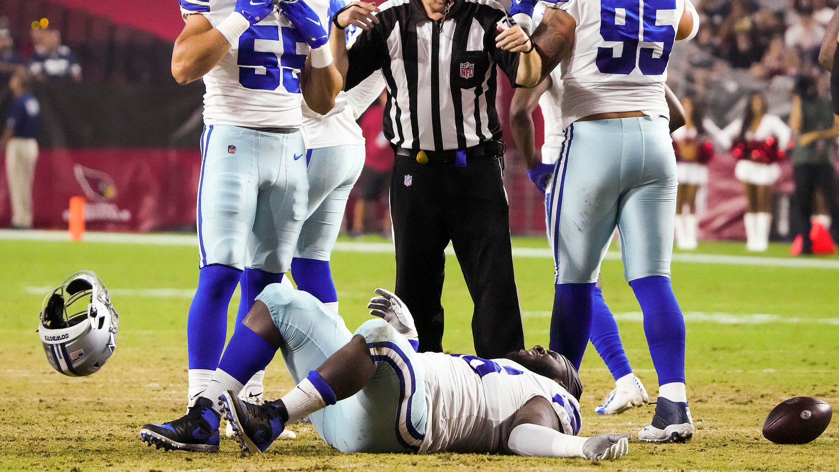Dallas Cowboys defensive tackle Neville Gallimore (96) tosses away his helmet after being injured during the first quarter of an NFL football game against the Arizona Cardinals as linebacker Leighton Vander Esch (55) looks on at State Farm Stadium on Friday, Aug. 13, 2021, in Glendale, Ariz. (Smiley N. Pool/The Dallas Morning News)