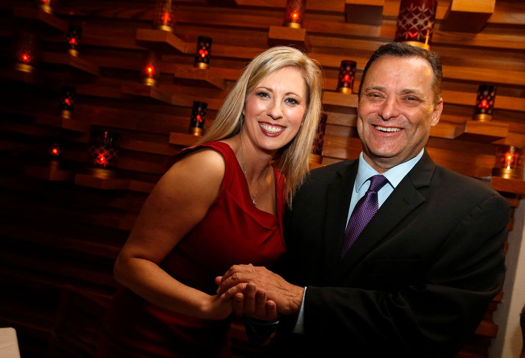 Ericka Downey (left) talks to Texas Tech coach Billy Gillispie pose for a portrait during a final four party for coaches at Ruth's Chris at the Grand Hyatt Riverwalk in San Antonio, Texas on March 30, 2018.  Ericka Downey, the Oklahoma mother of two and wife of Northeastern State University basketball coach Mark Downey, told The Dallas Morning News that she received confirmation Thursday from the Mayo Clinic that she will be able to donate one of her kidneys to Billy Gillispie.