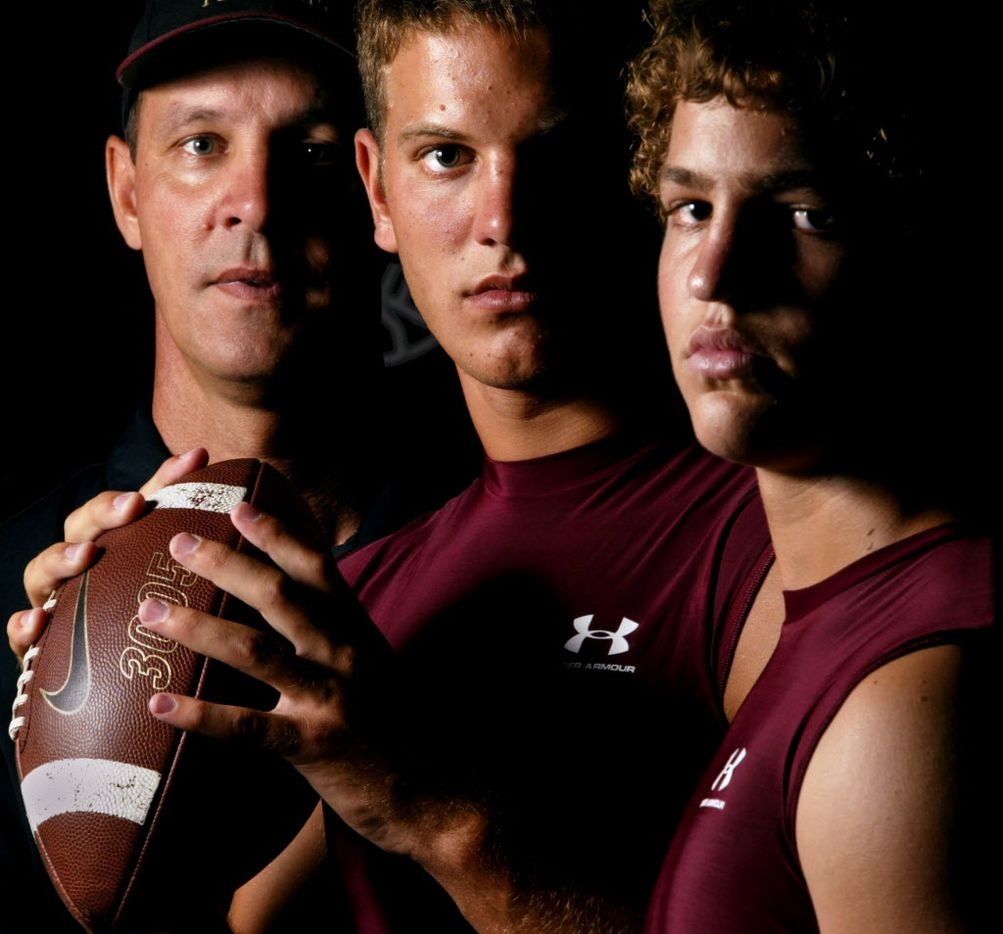 08-01-03 --- (L-R) Coach Sam Harrell poses for a portrait with his two quarterback sons, Graham Harrell, senior and Clark Harrell, sophomore at Ennis High School on Friday August 1, 2003.