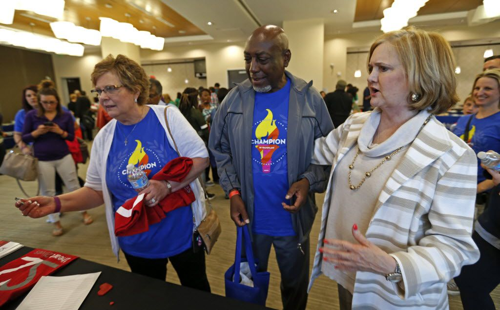 Judy Thompson (left) gets a T-shirt as Lowry Briley (center) and Kay Keeland look on during the Champions of Transplant annual Reunion event at Baylor Charles A. Sammons Cancer Center in Dallas, Sunday, April 17, 2016. Lowry and Kay are recipients of organs from Judy's daughter Davi Thompson. (Jae S. Lee/The Dallas Morning News)