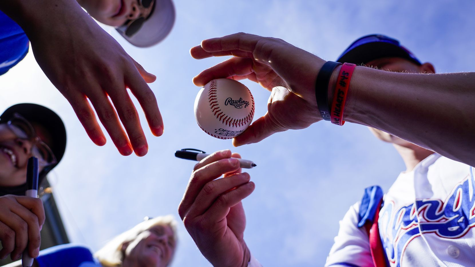 Texas Rangers outfielder Scott Heineman signs autographs before of a spring training game against the Chicago Cubs at Surprise Stadium on Thursday, Feb. 27, 2020, in Surprise, Ariz.