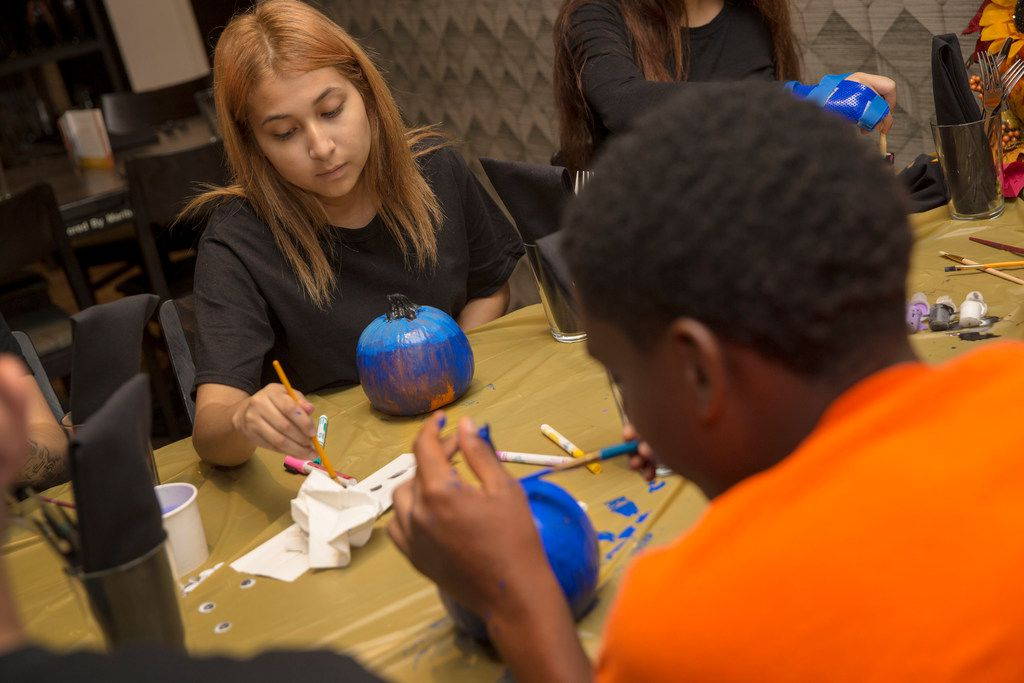 Employees Andrea, 15, left, and Michael, 17, paint pumpkins during an employee Thanksgiving dinner at Cafe Momentum.