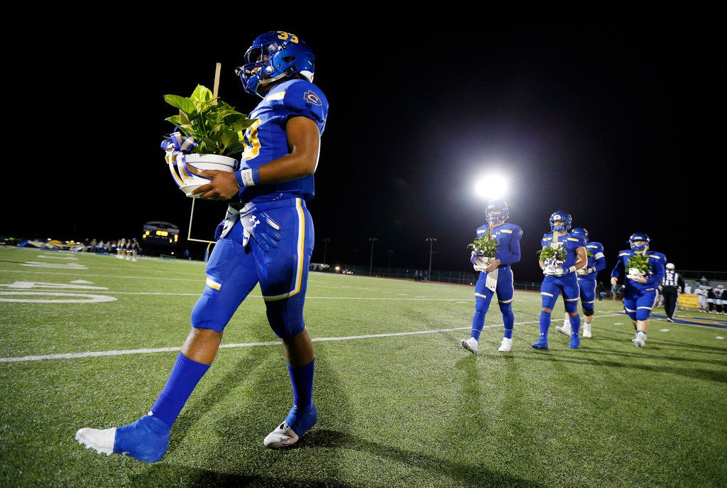 Community High defensive lineman Sean Outlaw (left) and his fellow captains carry plants given them by Dallas Roosevelt players during the coin toss at Community ISD Stadium in Nevada, Texas, Friday, November 8, 2019. They were playing with heavy hearts after four of their classmates were killed in a tragic vehicle accident earlier this week. (Tom Fox/The Dallas Morning News)