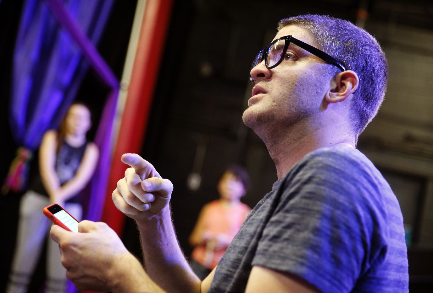 With his smartphone list of things to correct, director Derek Whitener asks for last-minute adjustments to be made during the Pippin dress rehearsal.