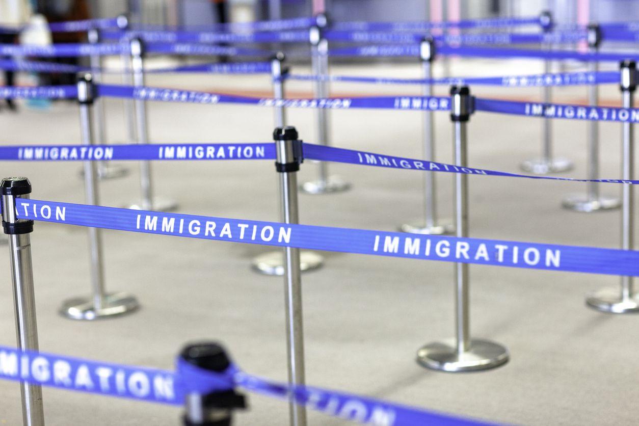 Línea en la sala de espera a aduanas e inmigración de un puerto de entrada a Estados Unidos.