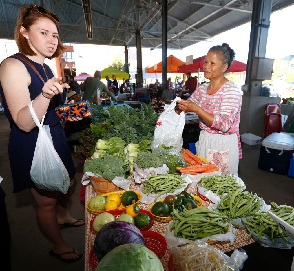 Customer Jessica Young points to the next item she wants to buy from Thongma Williams, at the Williams Farm booth in The Shed at the Dallas Farmers Market.