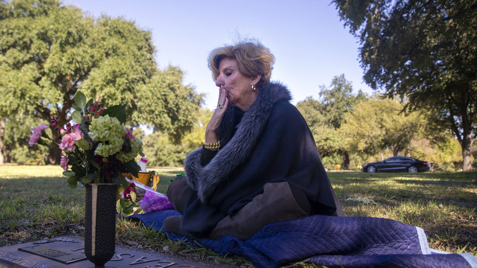 Shannon Dion kisses her parents' graves at Restland Memorial Park in Dallas on Oct. 31, 2019. She visits her parents' resting place once a month to freshen up the flowers and to speak with them. (Lynda M. Gonzalez/The Dallas Morning News)