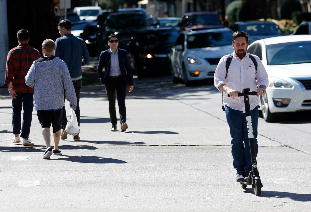 A man rides a Bird electric scooter in Uptown in Dallas, on Tuesday, October 23, 2018. (Vernon Bryant/The Dallas Morning News)
