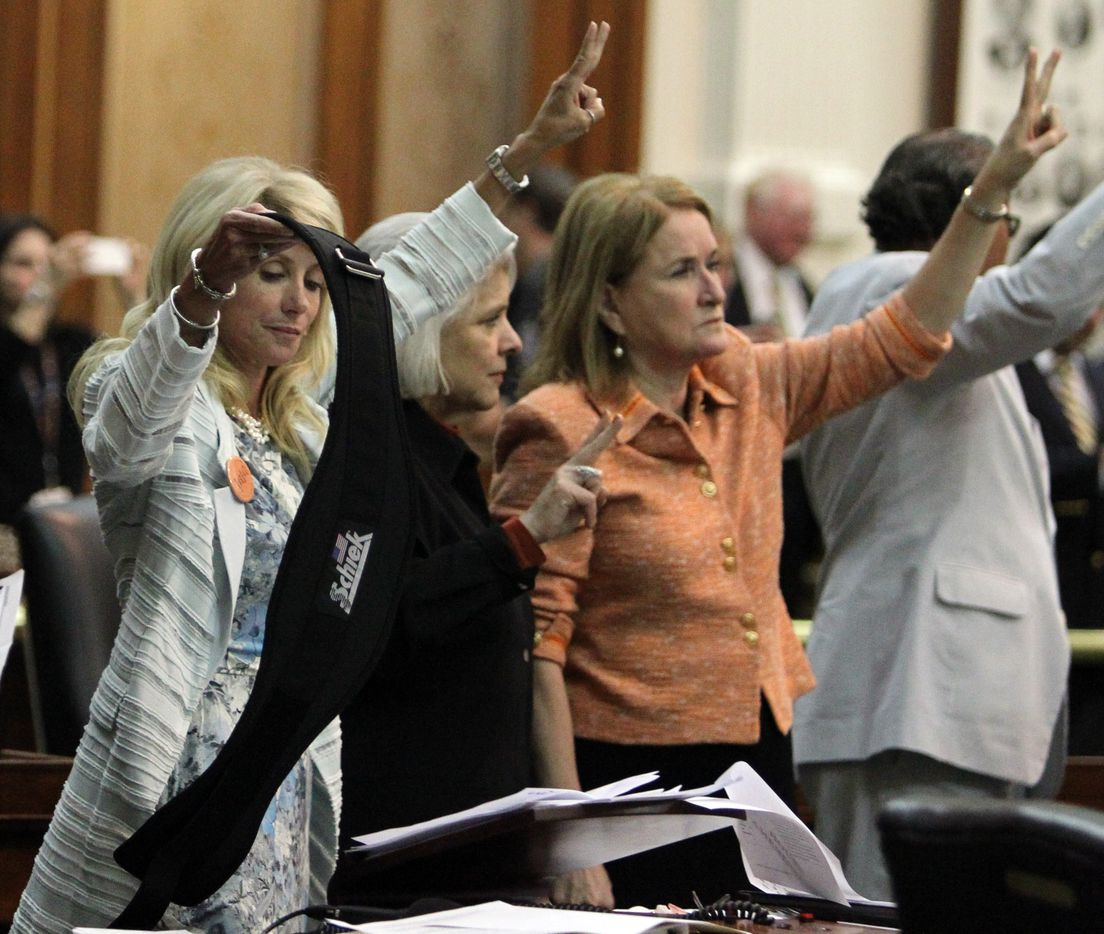 State Senator Wendy Davis takes off the back brace she put on, which caused a stir during her filibuster, as she celebrates with colleagues as bedlam breaks out near midnight on the final day of the legislative special session, as the Senate considers an abortion bill on Tuesday, June 25, 2013.  (Louis DeLuca/Dallas Morning News)