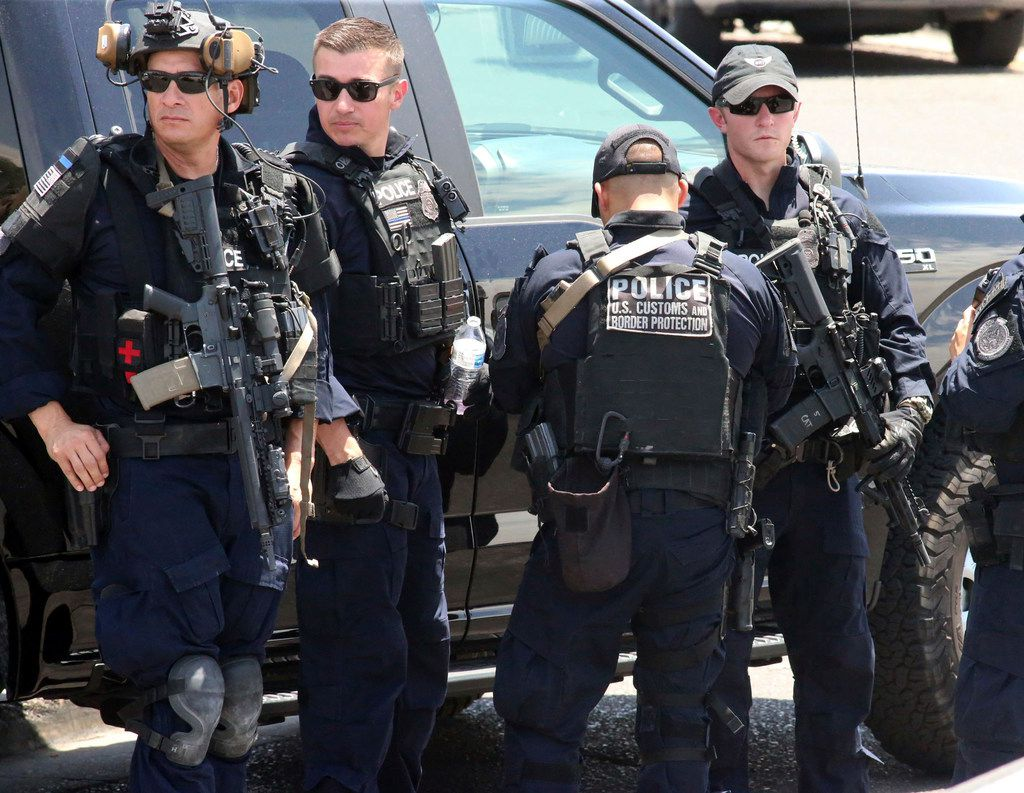 U.S. Customs and Border Protection officers gather near the scene of a shooting at a shopping mall in El Paso, Texas, on Saturday, Aug. 3, 2019.   Multiple people were killed and one person was in custody after a shooter went on a rampage at a shopping mall, police in the Texas border town of El Paso said.