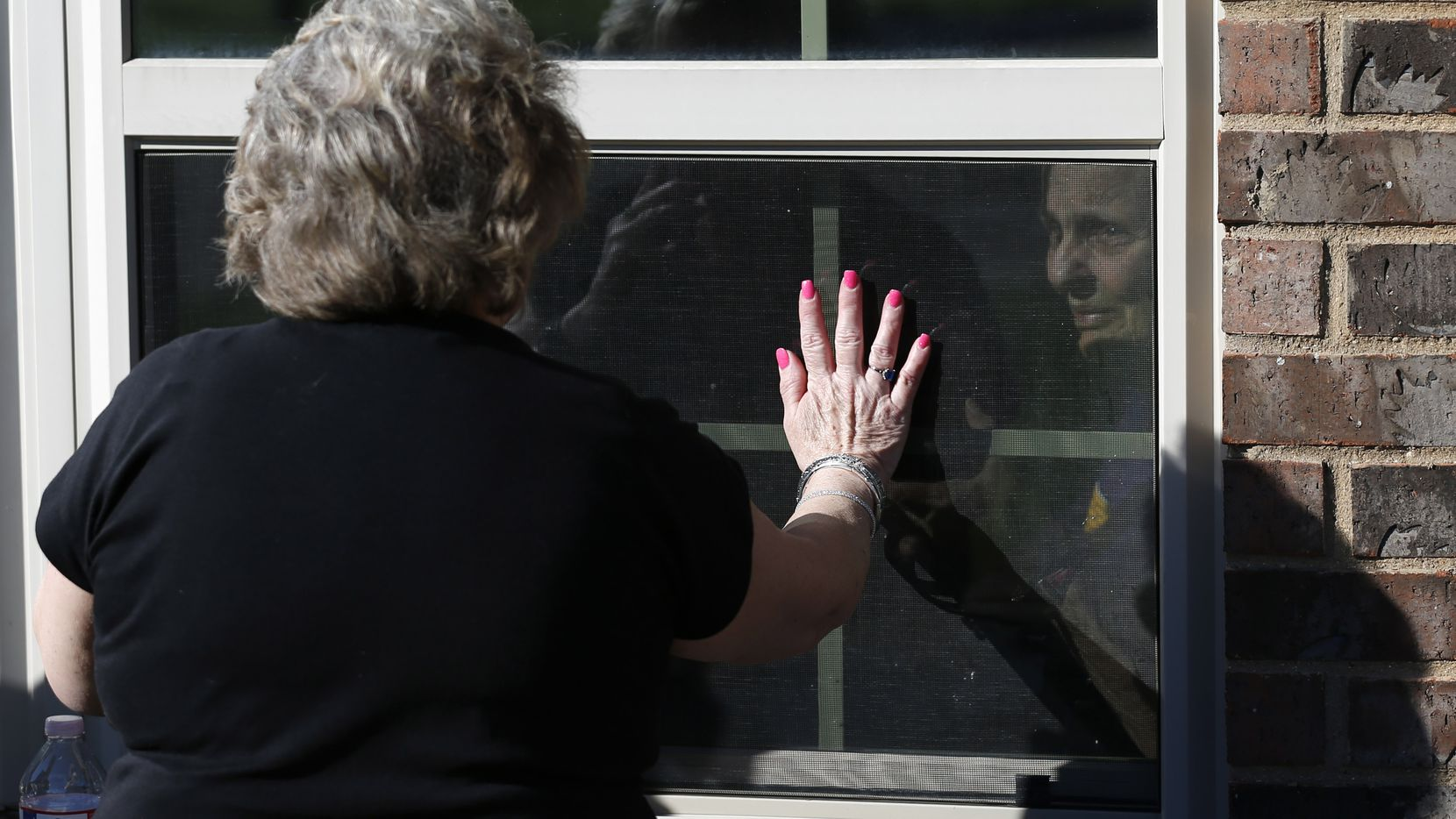 A daughter and her mother wave goodbye from opposites sides of the window at a Mansfield nursing home in March. New federal data show whether individual homes across Texas and the U.S. have reported any COVID-19 cases since May 1.