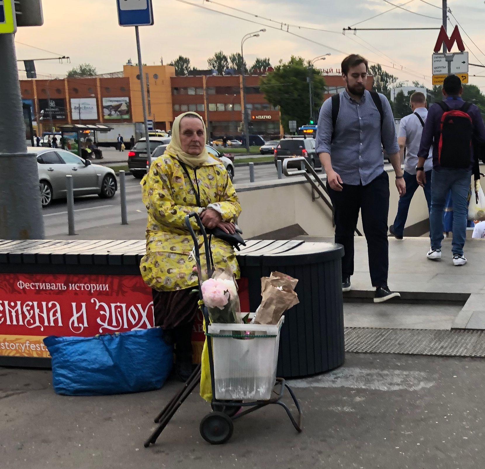 Señora vende flores en la puerta del metro de Moscú.