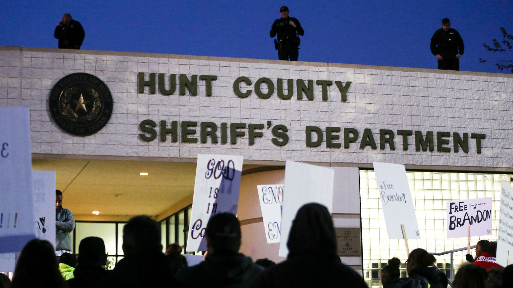 Roof top police watch as demonstrators gather at the Hunt County Sheriff's Department in downtown Greenville, Texas, Saturday, Nov. 2, 2019, calling for the release of Brandon Ray Gonzales, 23.  A witness claimed the suspect open fire at an off-campus college Halloween party in Texas, killing two people and injuring six more, according to an arrest affidavit. Gonzales is being held on a capital murder charge in the Hunt County Jail. His bail is set at $1 million.