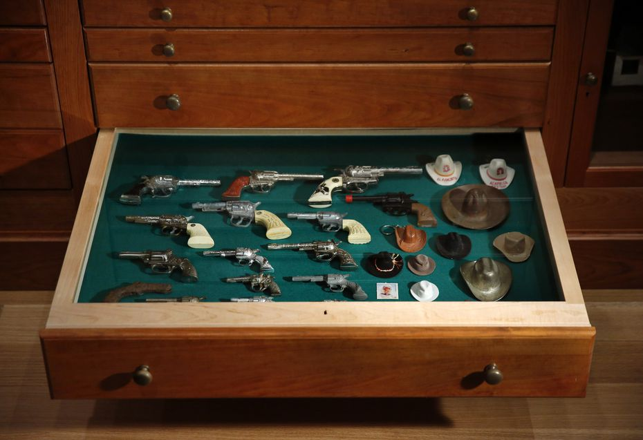 "Toy cowboy guns and hats occupy one drawer of the ""Texas Cabinet."""