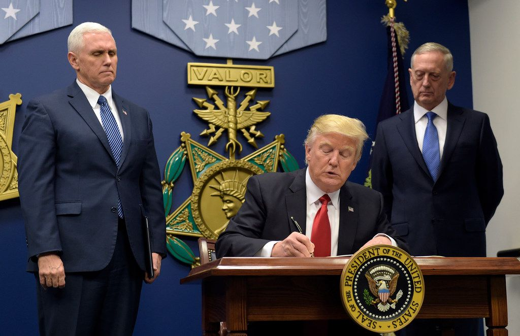 President Donald Trump  signed an executive action on extreme vetting at the Pentagon in Washington on Jan. 27, 2017, flanked by Vice President Mike Pence (left) and Defense Secretary James Mattis, who resigned in December 2018.