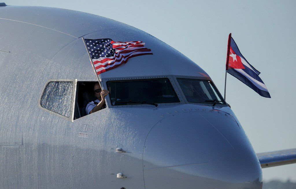 An American Airlines plane with U.S. and Cuba national flags is seen upon arrival at Jose Marti International Airport, becoming the first Miami-Havana commercial flight in 50 years, coinciding with the beginning of the tributes to late Cuban leader Fidel Castro, on November 28, 2016 in Havana. (Agence France-Presse)