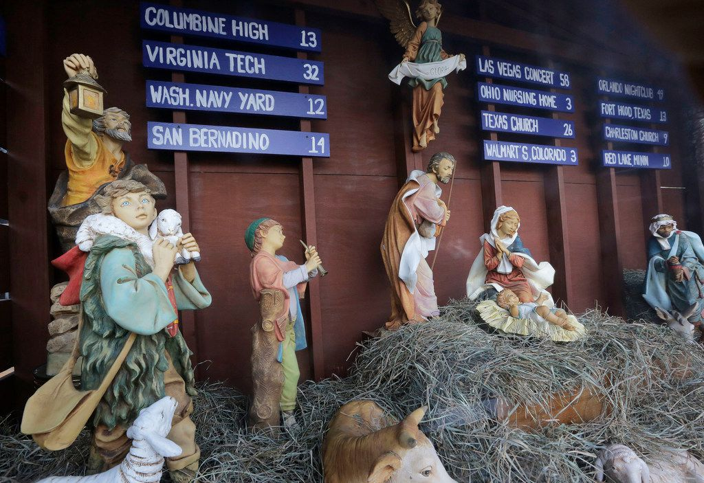 A traditional Nativity scene depicts the birth of Jesus in front of St. Susanna's Catholic Parish, in Dedham, Mass., but also includes signs listing U.S. mass shootings and the number of people killed at each.