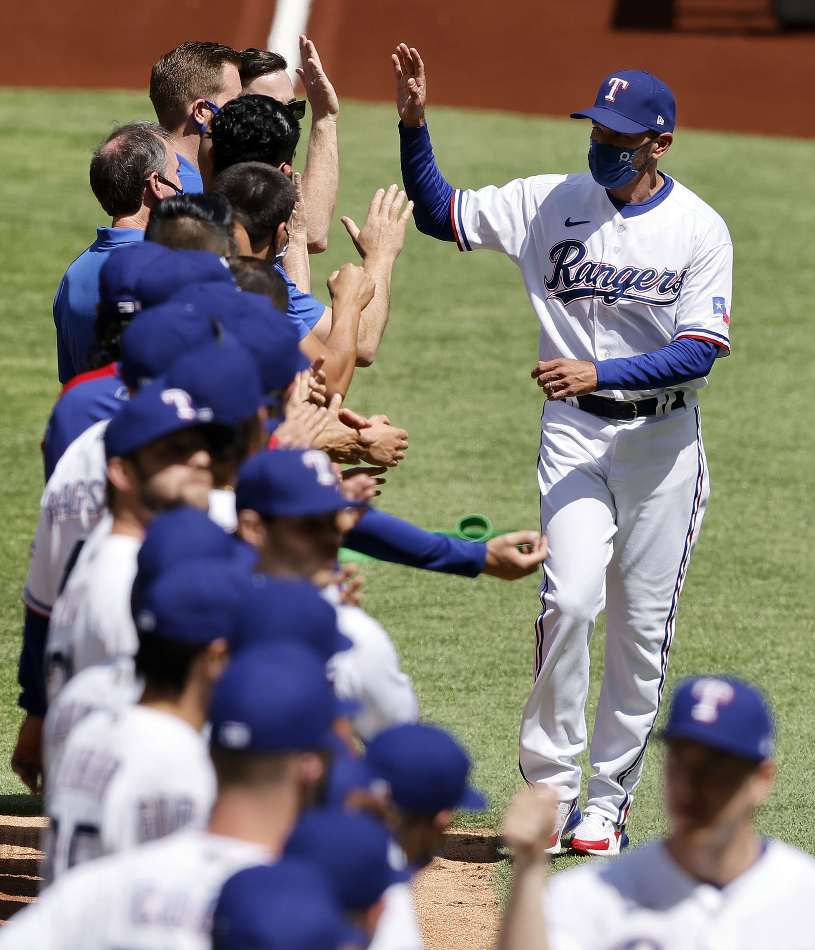 Texas Rangers manager Chris Woodward receives high-fives from his players during the team introduction at Globe Life Field in Arlington, Monday, April 5, 2021. The Texas Rangers were facing the Toronto Blue Jays in their home opener. (Tom Fox/The Dallas Morning News)