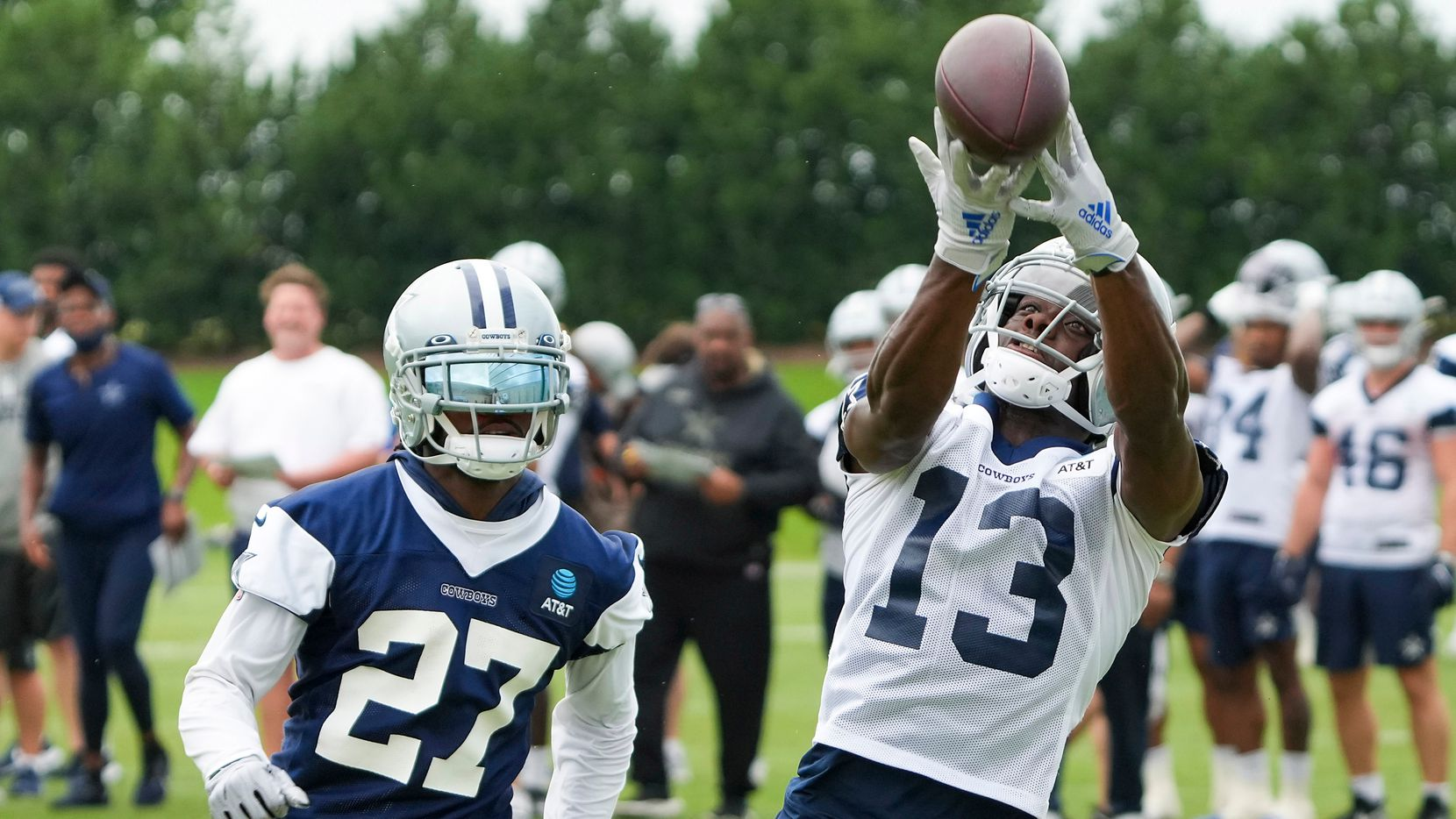 Dallas Cowboys wide receiver Michael Gallup (13) reaches for a pass as cornerback Trevon Diggs (27) defends during a minicamp practice at The Star on Wednesday, June 9, 2021, in Frisco. (Smiley N. Pool/The Dallas Morning News)